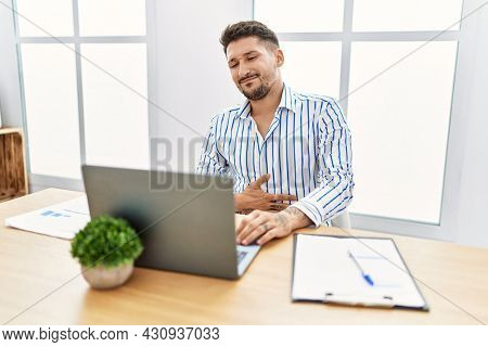 Young handsome man with beard working at the office using computer laptop with hand on stomach because indigestion, painful illness feeling unwell. ache concept.