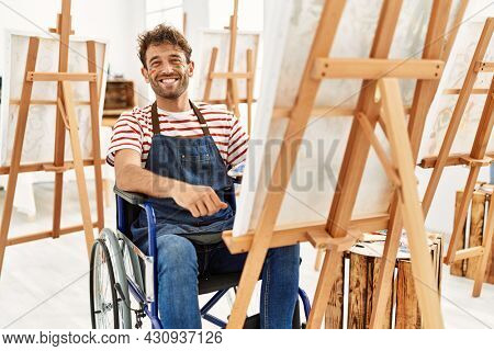 Young handsome man with beard at art studio sitting on wheelchair looking positive and happy standing and smiling with a confident smile showing teeth