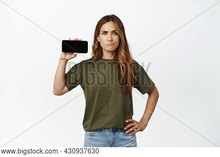 Portrait Of Displeased Frowning Woman Showing Horizontal Smartphone Screen, Demonstrate An App Or Ba