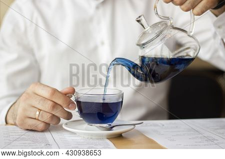 A Man In A White Shirt Pours Blue Chinese Tea From A Transparent Teapot Into A Mug