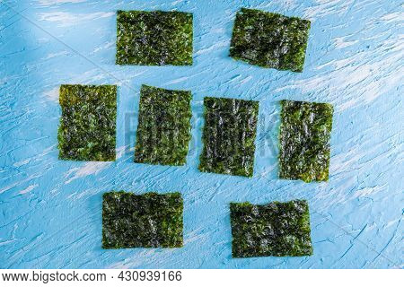 Crispy Dried Seaweed, Nori Chips Piece Of Roasted Seaweed Sheet On A Blue Background. Healthy Food C