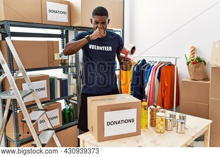 Young african american volunteer man packing donations box for charity feeling unwell and coughing as symptom for cold or bronchitis. health care concept.