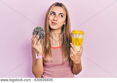 Beautiful hispanic woman eating doughnut and drinking coffee smiling looking to the side and staring away thinking.