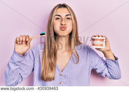 Beautiful hispanic woman holding denture and toothbrush puffing cheeks with funny face. mouth inflated with air, catching air.