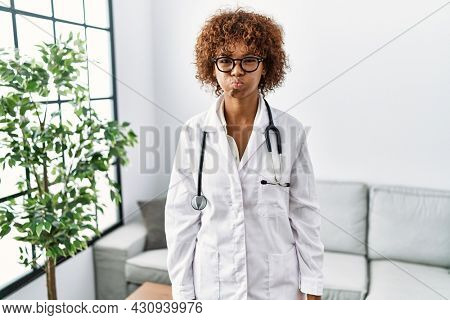 Young african american woman wearing doctor uniform and stethoscope puffing cheeks with funny face. mouth inflated with air, crazy expression.