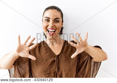 Young brunette woman standing over isolated background showing and pointing up with fingers number ten while smiling confident and happy.