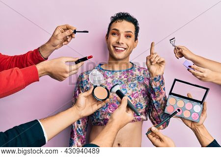 Handsome man wearing make up with make up cosmetics around smiling with an idea or question pointing finger up with happy face, number one
