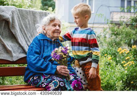 Grandparents Day, Reunited Family, Togetherness. Senior Old Grandma Hugs Grandson Outdoors. Grandchi