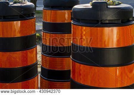 Orange And Black Striped Plastic Roadwork Barrels Placed Near A Road Repair Site To Alert Traffic