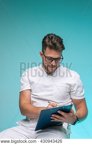 Professional Young Male Physician Practitioner In Glasses, Medical Uniform Writing Doctor Report. Jo