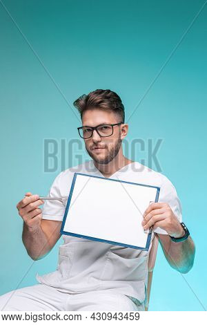 Professional Male Physician Practitioner In Glasses Pointing On Blank Space On White Sheet. Doctor R