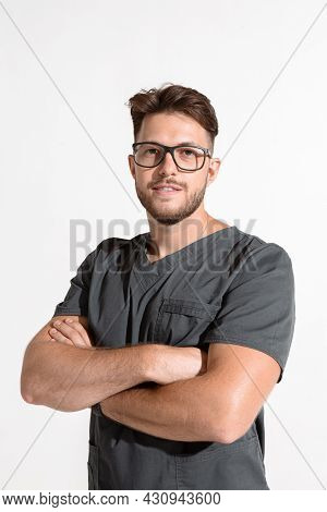 Professional Young Male With Arms Crossed, Physician Practitioner In Glasses And Medical Uniform On