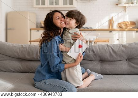Adorable Little Boy Congratulating Mom With International Mother Day Or Birthday Embracing Happy Fem