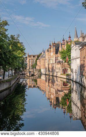 Brugge, Flanders, Belgium - August 4, 2021: Blinde Ezelstraat Brick Bridge And Sunlighted Palace Bui