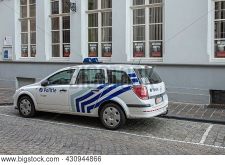 Brugge, Flanders, Belgium - August 4, 2021: White And Blue Opel Police Station Wagon Parked In Stree