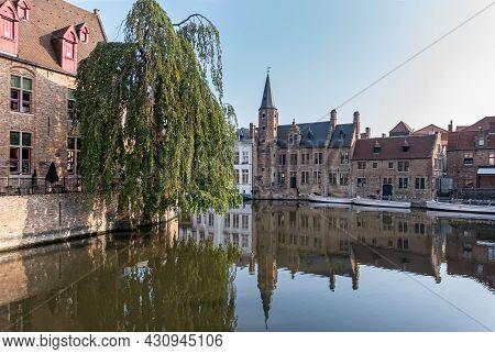 Brugge, Flanders, Belgium - August 4, 2021: Quiet Dijver Canal Reflects Brown Stone Huidevettershuis