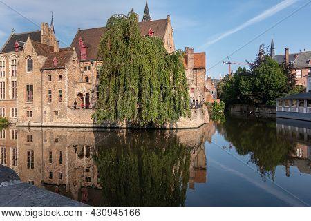 Brugge, Flanders, Belgium - August 4, 2021: Quiet Dijver Reflects Sunlit Brown Brick Buildings Of Wo