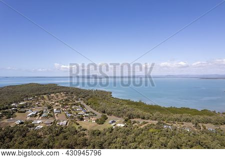Drone Aerial Over A Small Seaside Township Nestled Amongst Bushland Beside A Blue Sea