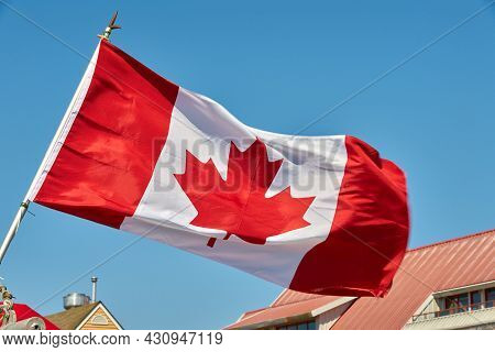 Canadian Flag Blue Sky. A Canadian Flag Flapping In A Stiff Breeze On A Sunny Day. Canada.