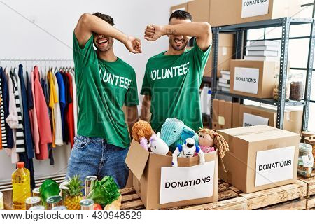Young gay couple wearing volunteer t shirt at donations stand smiling cheerful playing peek a boo with hands showing face. surprised and exited