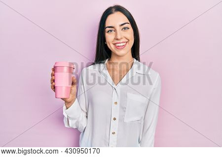 Beautiful woman with blue eyes drinking a take away cup of coffee looking positive and happy standing and smiling with a confident smile showing teeth