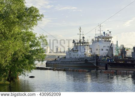 Two Tugs With A Barge At A Floating Pier On The River In The City Of Novosibirsk. Water Surface, Tre
