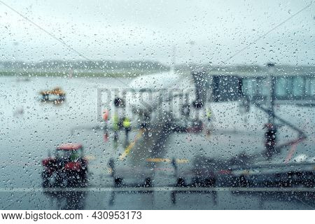 Modern plane located on aerodrome behind wet glass on rainy day in airport