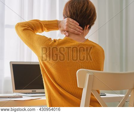 Back View Of Anonymous Female Sitting At Desk And Feeling Pain In Neck. Disadvantages Of Remote Work