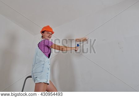 Standing On A Stepladder Painting The Wall
