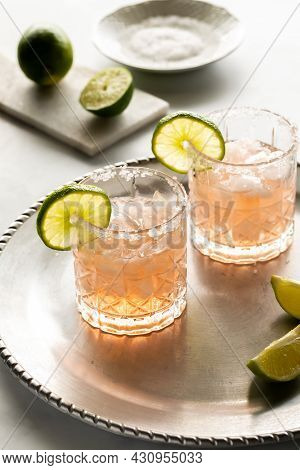 Two Margarita Mocktails Garnished With Lime And Salted Rims, Ready For Drinking.