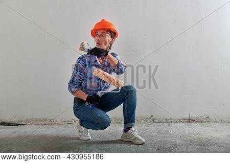 Bright Orange Hard Hat On A Repairwoman In Jeans