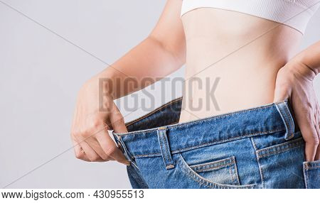 Close Up Slim Woman Measuring Her Thin Waist. Healthcare And Woman Diet Lifestyle Concept To Reduce