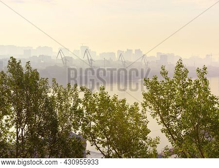 A Foggy Morning On The Ob River In Novosibirsk. The Shore Of A Big City With Port Cranes In A Yellow