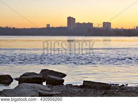 Before Sunrise On The Ob River. Stones In Blue Water. Silhouette Of High Houses On The Horizon. Novo