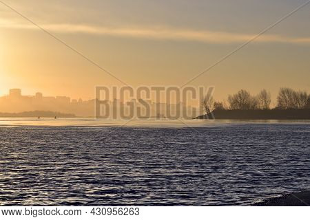 Golden Dawn Over The River Ob. The Trees And The City Of Novosibirsk Appear From The Fog On The Hori