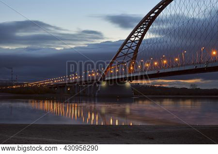 The Bugrinsky Highway Bridge Across The Ob River Stretches To The Horizon. Street Lights. Reflection