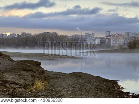 Novosibirsk Foggy Morning On The Rocky Bank Of The Ob River. Intertwining Banks, Houses And Trees Ar