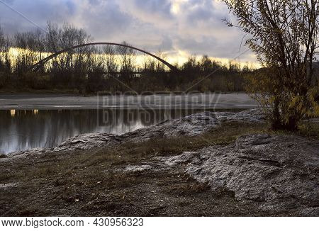 The Rocky Bank Of The Ob River. Autumn Trees. Arch Of The Bugrinsky Bridge. Dawn With Golden And Lil