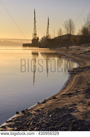 River Bank With Cranes At Dawn. The Bend Of The Coastline, Cranes In The Distance, Reflection In The