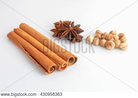 Cinnamon Sticks, Anise Stars, And Dry Cardamom On A White Background. Selective Focus