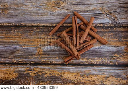 Aromatic Dry Cinnamon Sticks On Wooden Table Background, Top View