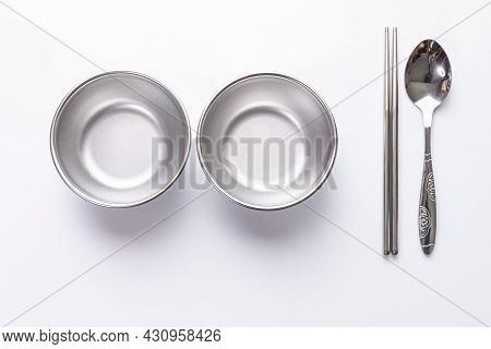 Two Small Aluminum Empty Bowls, Spoons, And Chopsticks On White Background.