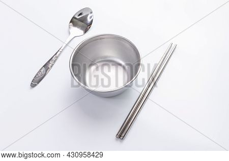 Small Aluminum Empty Bowls, Spoons, And Chopsticks On White Background. Selective Focus
