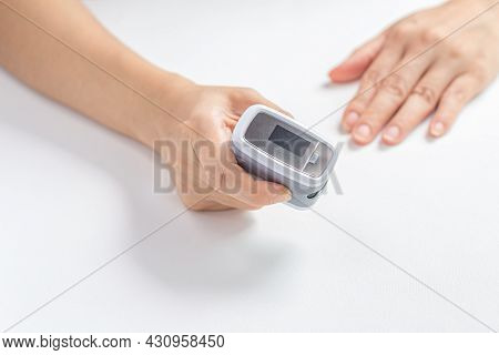 Female Hands Hold The Digital Pulse Oximeter For Use With Measures The Patient's Pulse And Oxygen Sa