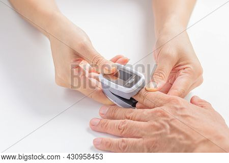 Female Hands Measures The Patient's Pulse And Oxygen Saturation (spo2) For Middle Aged Man Using A D