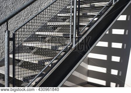 An Exterior Stairway At A Building With A Metal Railing In Bright Morning Sunlight