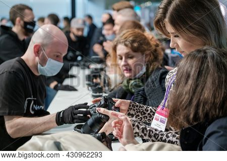 Moscow - April 21, 2021: Crowd of professional photographers in masks checking and choosing photo camera lenses in technology store during pandemic