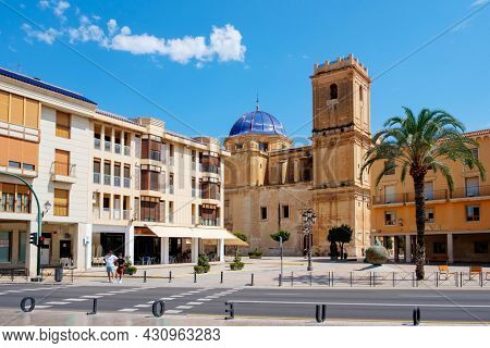 Elche, Spain - July 26, 2021: A view over the Palau Square in Elche, Spain, highlighting the dome and the belltower of the Basilica of Santa Maria church, dedicated to the Virgin Mary