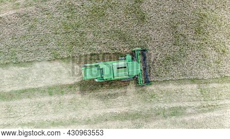 Green Combine Harvester Harvests Barley In The Field In Summer. Aerial View. Harvest Time.