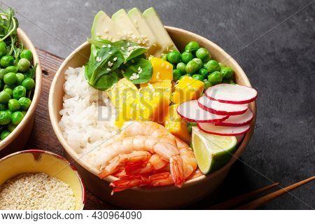 Poke bowl with shrimps, avocado and mango. Traditional hawaiian meal